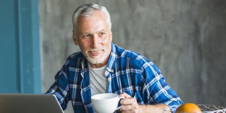 hombre-sonriente-que-sostiene-taza-cafe-que-mira-lejos-computadora-portatil-tabla_23-2147859788.jpg
